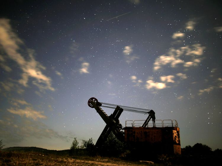 A meteor streaks past stars in the night sky above an excavator at an abandoned coal mine in the village Moscanica, Bosnia and Herzegovina, August 12, 2017. REUTERS/Dado Ruvic
