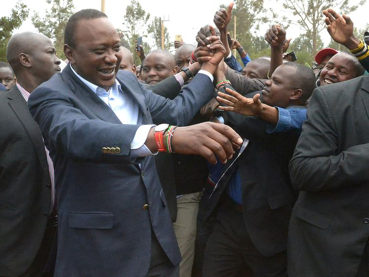 Kenya's President Uhuru Kenyatta greets supporters after voting