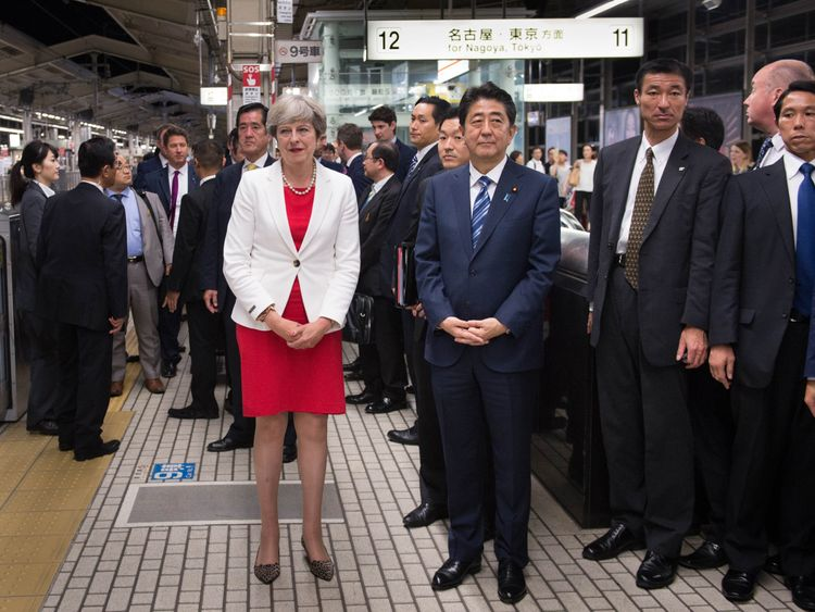 Theresa May and Shinzo Abe wait for a bullet train to Tokyo