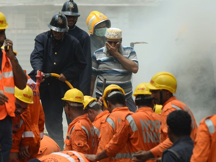 Rescue workers look for survivors at the site of a building collapse in Mumbai