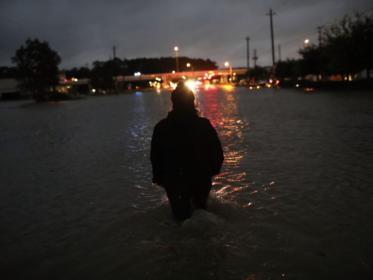 A Houston resident walks through waist deep water after evacuating her home