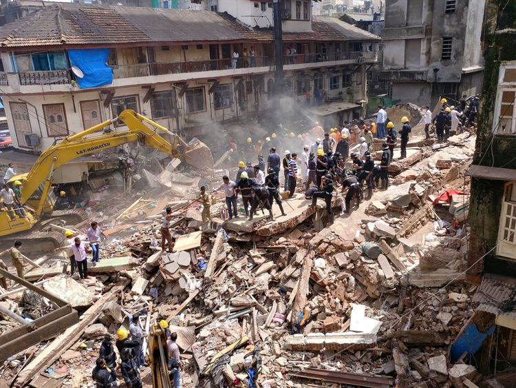 Firefighters and rescue workers search for survivors at the site of a collapsed building in Mumbai