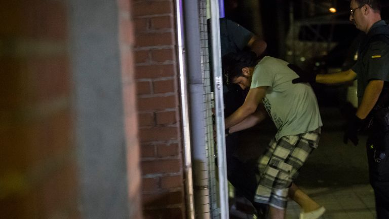 Another of the suspects is ushered into a building in Madrid