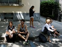 People sit on a sidewalk after the earthquake hit