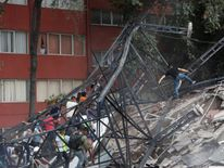 People climb over the debris of a collapsed building