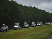 A line of utility trucks drive north on Interstate 75 in Florida