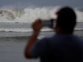A man photographs the waves before the arrival of Maria in Guayama, Puerto Rico