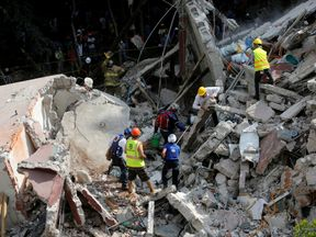 Rescue personnel remove rubble at a collapsed building while searching for people after an earthquake hit Mexico City, Mexico September 19, 2017