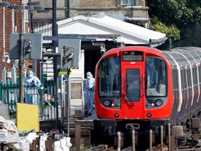 A forensic tent is seen next to the stopped tube train at Parsons Gree
