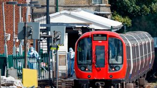 Police forensics officers work alongside an underground tube train at Parsons Green