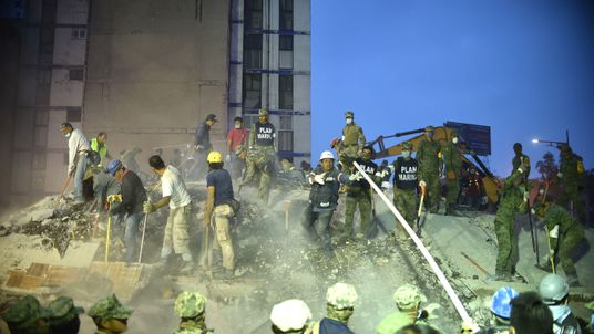 Rescuers, firefighters, policemen, soldiers and volunteers remove rubble and debris from a flattened building