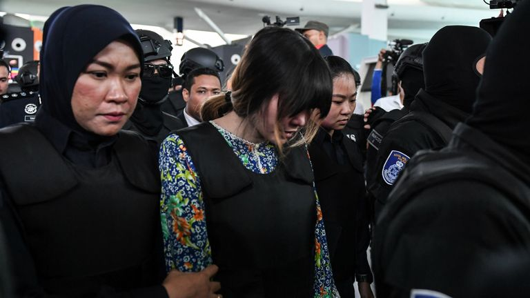 Vietnamese defendant Doan Thi Huong (C) is escorted by police personnel towards the low-cost carrier Kuala Lumpur International Airport 2 (KLIA2) in Sepang during a visit to the scene of the murder as part of the Shah Alam High Court trial process on October 24, 2017, for her alleged role in the assassination of Kim Jong-Nam