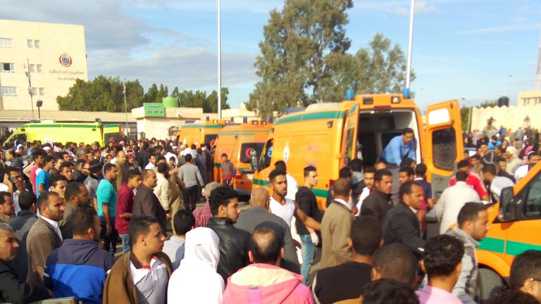 Egyptians crowd around ambulances following the gun and bomb attack