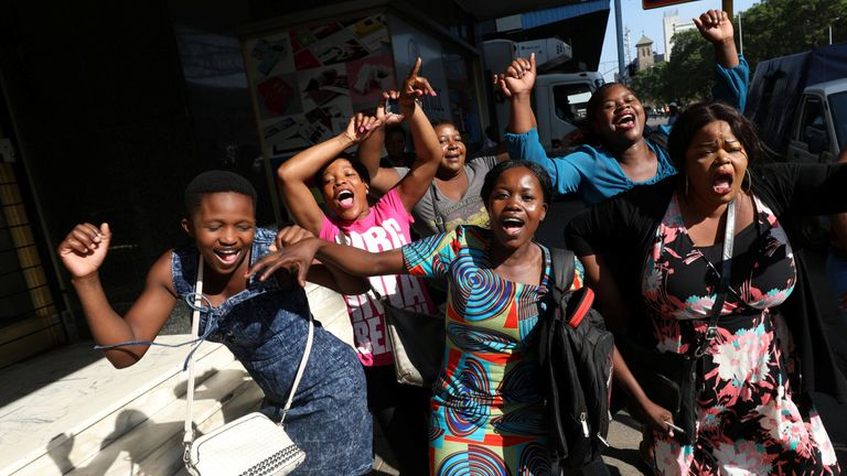 Zimbabweans celebrate in the morning sun after President Robert Mugabe resigned in Harare