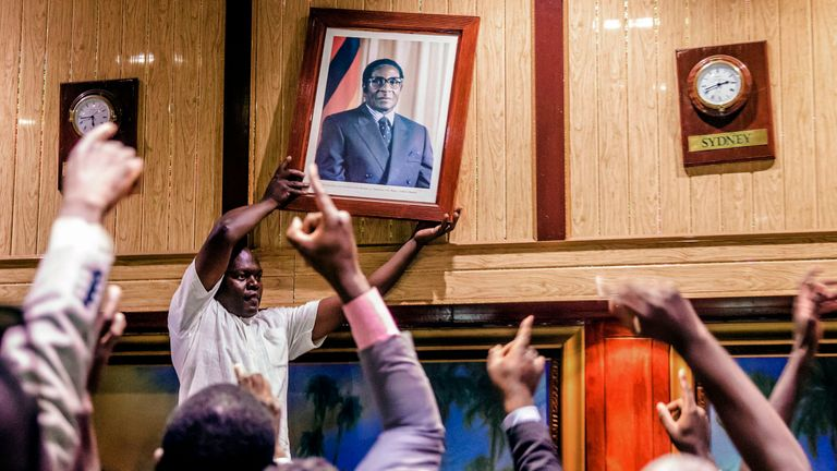 Mugabe's portrait is removed from a wall in Harare's International Conference centre