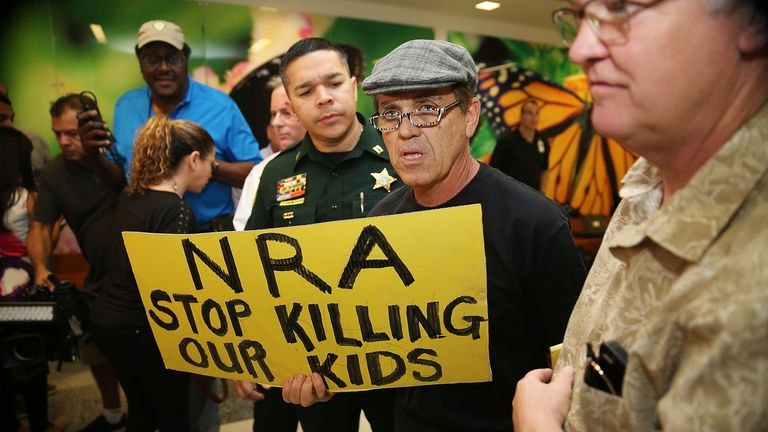 A protester holds a sign that reads 'NRA Stop Killing Our Kids' following the Florida massacre
