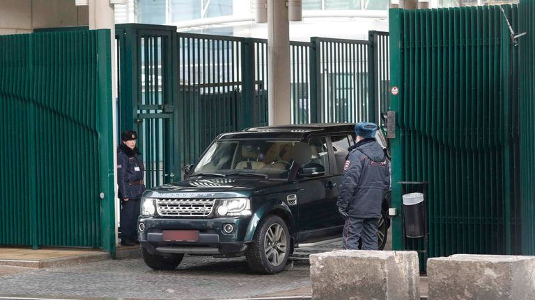 Police officers watch a car leaving the British embassy compound in Moscow