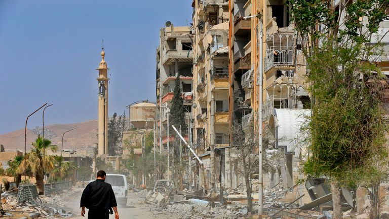 A picture taken during a Syrian army-organised tour on April 20, 2018 shows a man walking down a street past destruction in the Eastern Ghouta town of Douma on the outskirts of the capital Damascus
