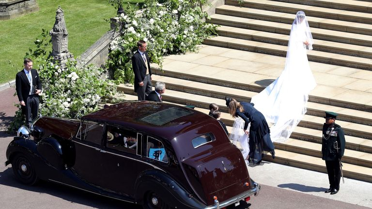 Clare Waight Keller assisting the bride with her train on the steps of St George's Chapel