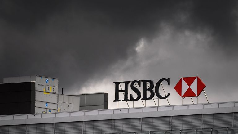 A sign of international banking and financial services holding company HSBC is seen under black clounds on the top of a building on March 1, 2019 in Geneva