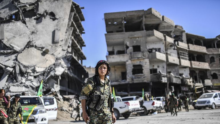 """TOPSHOT - Kurdish female fighters of the Syrian Democratic Forces (SDF) gather during a celebration at the iconic Al-Naim square in Raqa on October 19, 2017, after retaking the city from Islamic State (IS) group fighters. The SDF fighters flushed jihadist holdouts from Raqa's main hospital and municipal stadium, wrapping up a more than four-month offensive against what used to be the inner sanctum of IS's self-proclaimed """"caliphate"""". / AFP PHOTO / BULENT KILIC (Photo credit should read BULENT KI"""