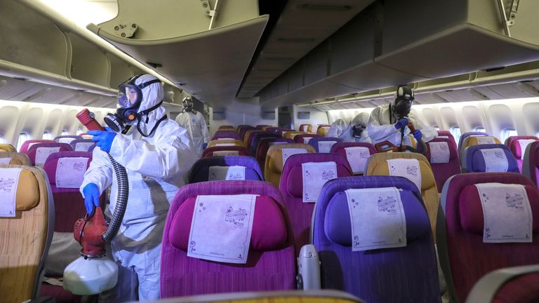 Members of the Thai Airways crew disinfect the cabin of an aircraft of the national carrier during a procedure to prevent the spread of the coronavirus at Bangkok's Suvarnabhumi International Airport