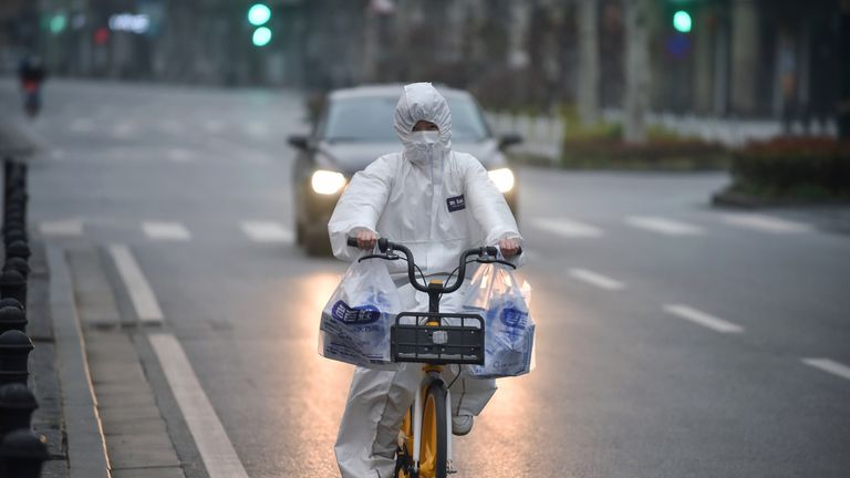 This photo taken on February 27, 2020 shows a resident wearing a protective suit riding a bicycle in Wuhan in China's central Hubei province. - China reported 44 more deaths from the novel coronavirus epidemic on February 28 and 327 fresh cases, the lowest daily figure for new infections in more than a month. (Photo by STR / AFP) / China OUT (Photo by STR/AFP via Getty Images)