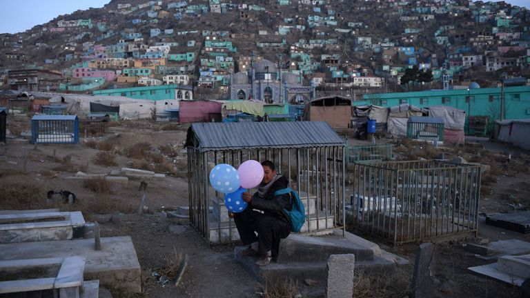 An Afghan balloon seller waits for customers in a cemetery in Kabul on December 17, 2019