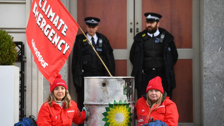 Police officers stand near activists locked to dirty oil barrels who have blocked BP's headquarters to mark the first day of the oil giant's new chief executive