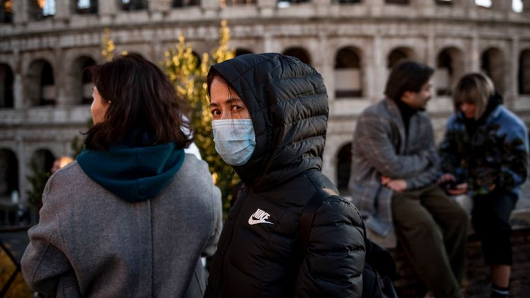 Chinese tourists wearing face masks visit the Colosseum area on February 6, 2020 in Rome, Italy