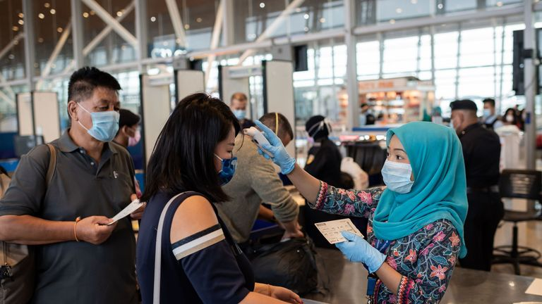 In this picture taken on February 14, 2020, a Malaysia Airlines hostess (R) wearing a protective face mask checks the temperature of Chinese passengers before they board a flight to Beijing at the Kuala Lumpur International Airport in Kuala Lumpur