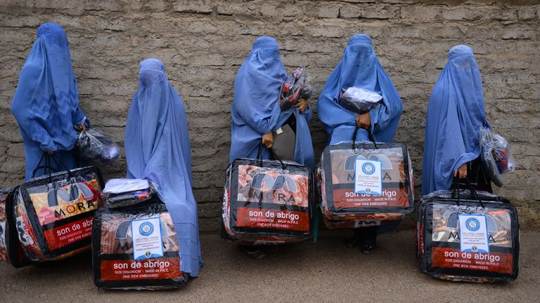 In this photograph taken on December 19, 2019, Afghan burqa-clad women stand with aid items received from a charity in Herat