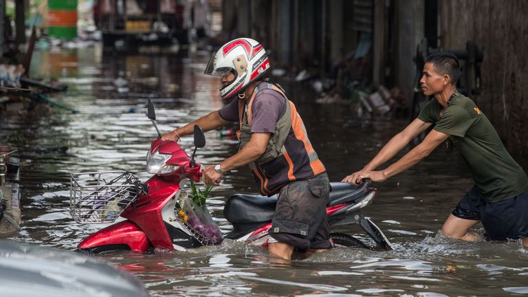 A man helps push a dead motorcycle taxi on a flooded street in Bangkok in 2017