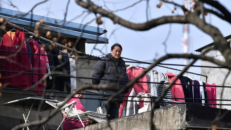 "A man stands next to laundry on a balcony at a residential compound in Wuhan, the epicentre of the novel coronavirus disease (COVID-19) outbreak, Hubei province, China, March 10, 2020. REUTERS     SEARCH ""WUHAN HOMES"" FOR THIS STORY. SEARCH ""WIDER IMAGE"" FOR ALL STORIES.  CHINA OUT."