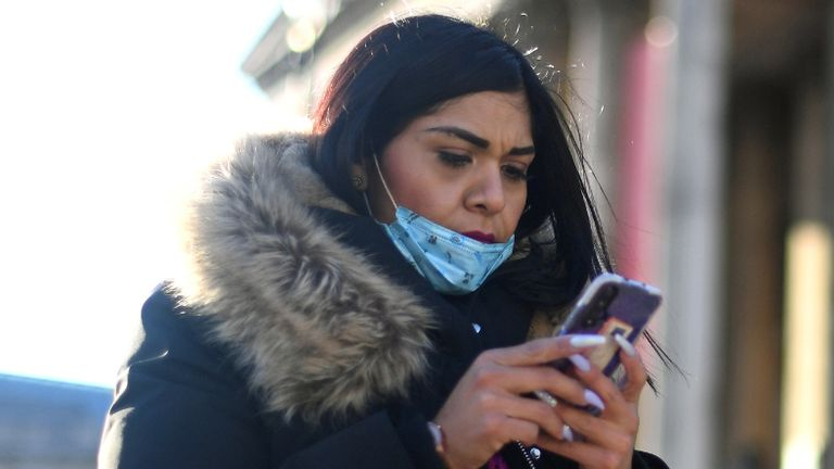 A woman wearing a face mask on her phone outside the National Gallery in Trafalgar Square, London.