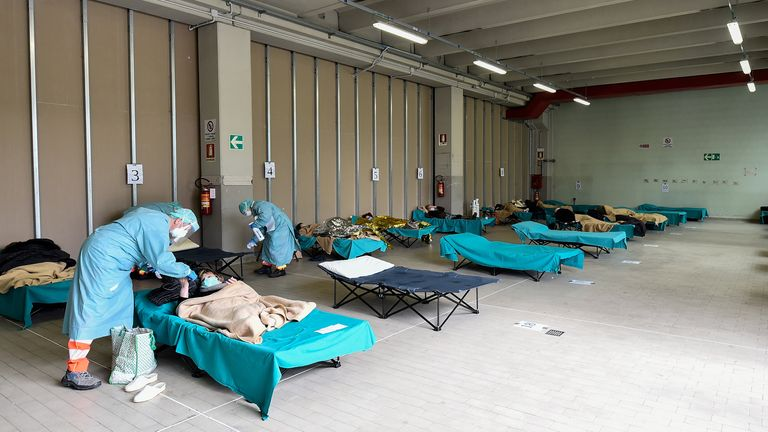 Medical personnel wearing protective face masks helps patients inside the Spedali Civili hospital in Brescia, Italy