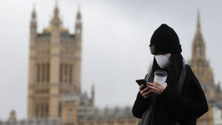 A pedestrian wearing a face mask walks along Westminster Bridge in front of the Houses of Parliament in London on March 12, 2020. - The British government was expected Thursday to implement the second phase of its plan to deal with the coronavirus outbreak but rejected calls for parliament to be suspended after an MP tested positive. (Photo by ISABEL INFANTES / AFP) (Photo by ISABEL INFANTES/AFP via Getty Images)