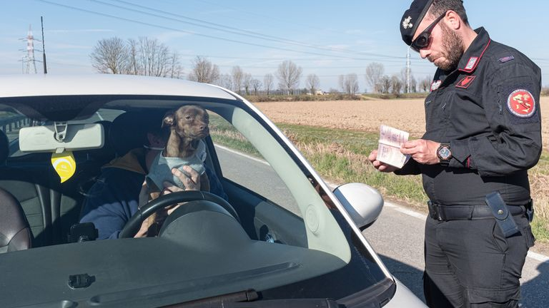 Military police check documents at a 'red zone' checkpoint in San Fiorano, southeast of Milan