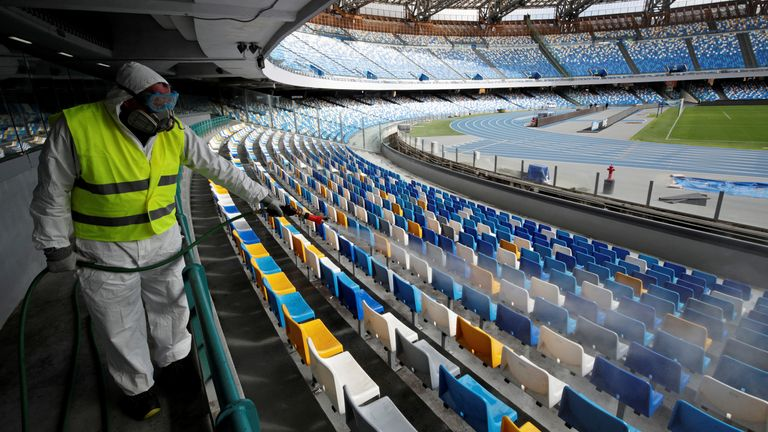 A cleaner sanitises seats at the San Paolo stadium