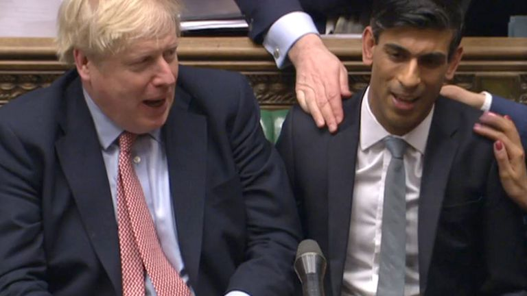 Chancellor Rishi Sunak (right) sits down after delivering his Budget in the House of Commons, London