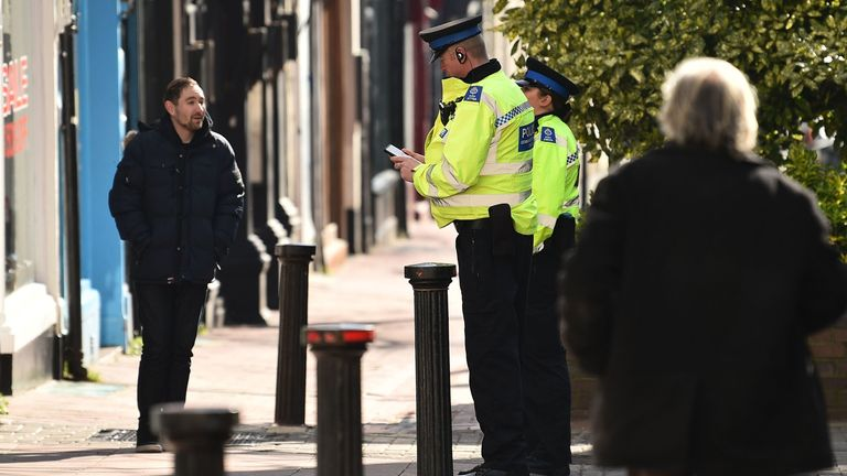 """Police community support officers talk to a man on a street in Brighton, southern England on March 24, 2020 after the British government ordered a lockdown to help stop the spread of coronavirus. - Britain was under lockdown March 24, its population joining around 1.7 billion people around the globe ordered to stay indoors to curb the """"accelerating"""" spread of the coronavirus. (Photo by Glyn KIRK / AFP) (Photo by GLYN KIRK/AFP via Getty Images)"""