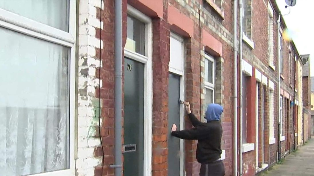 A decorator paints over some doors previously painted red