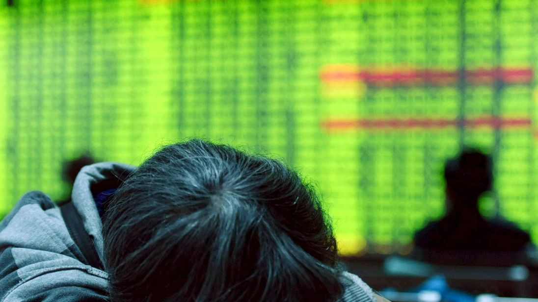 An investor rests in front of an screen showing stock information