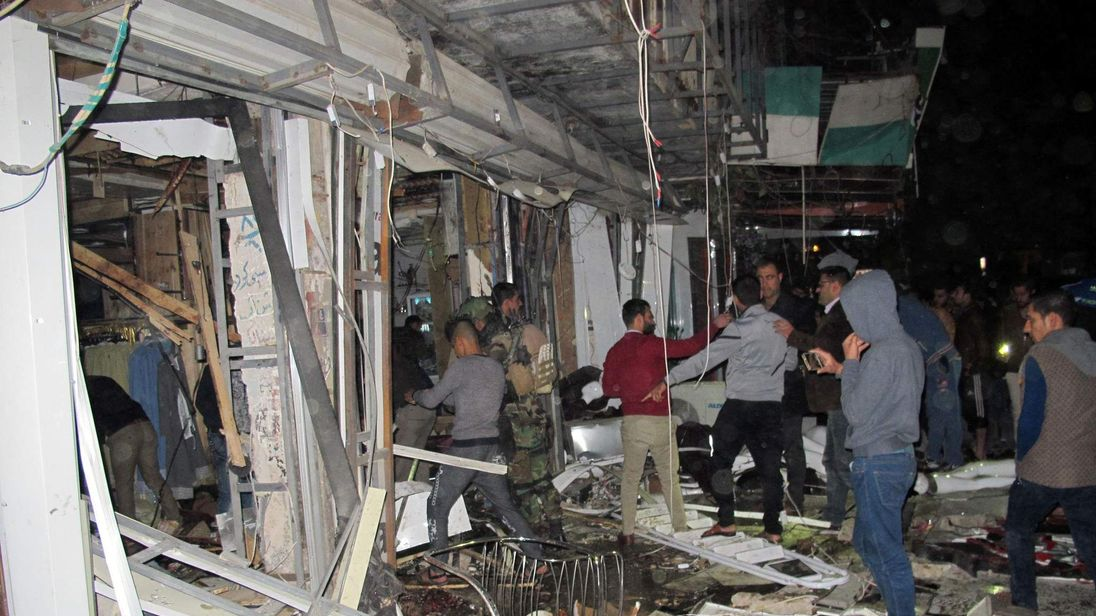 Iraqis gather at the site of an attack in eastern Baghdad