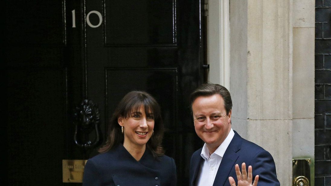 Britain's Prime Minister David Cameron waves as he arrives with his wife Samantha at Number 10 Downing Street in London