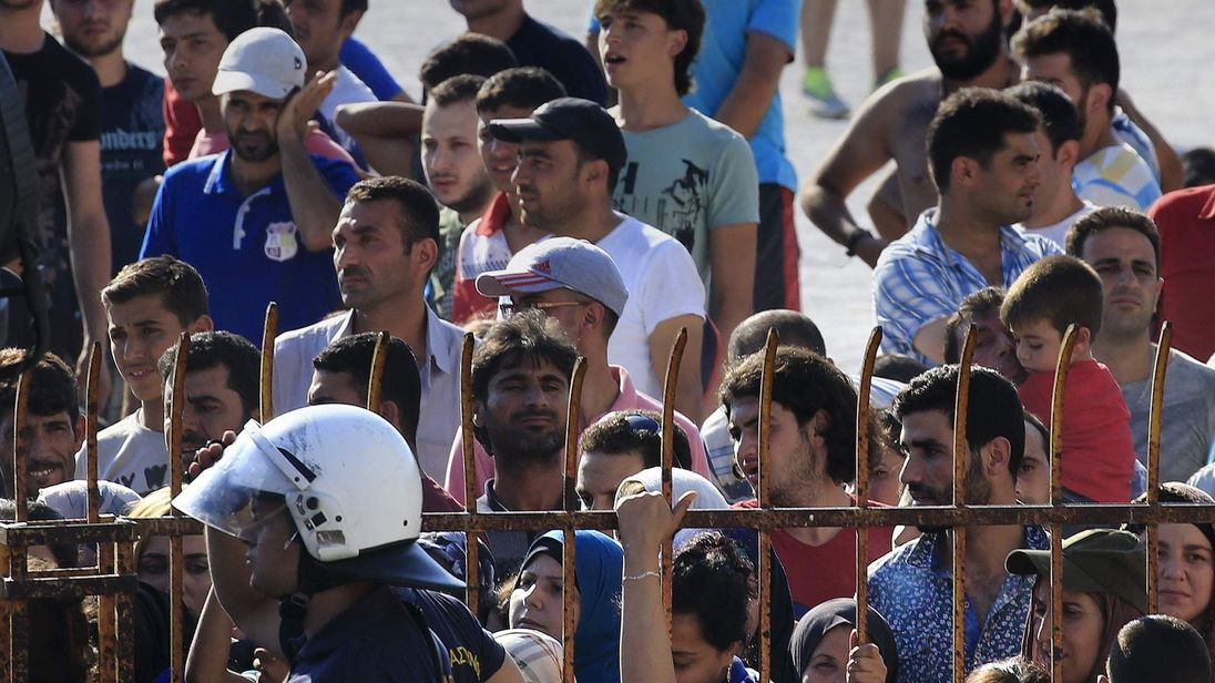 A Greek riot police officer stands guard as migrants and refugees wait to be registered at the national stadium of the Greek island of Kos