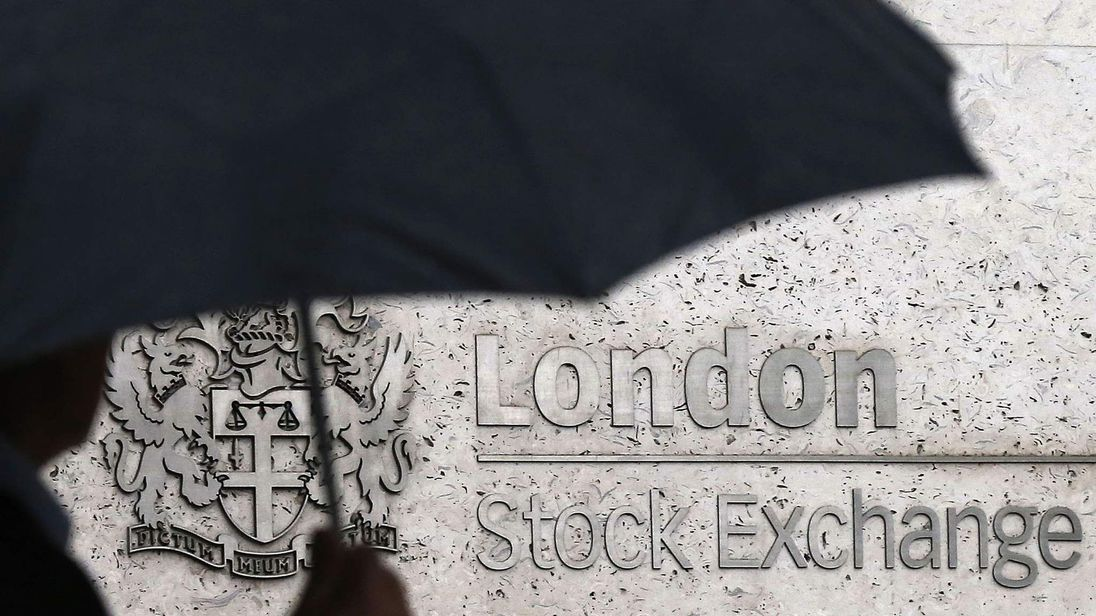 A man shelters under an umbrella as he walks past the London Stock Exchange