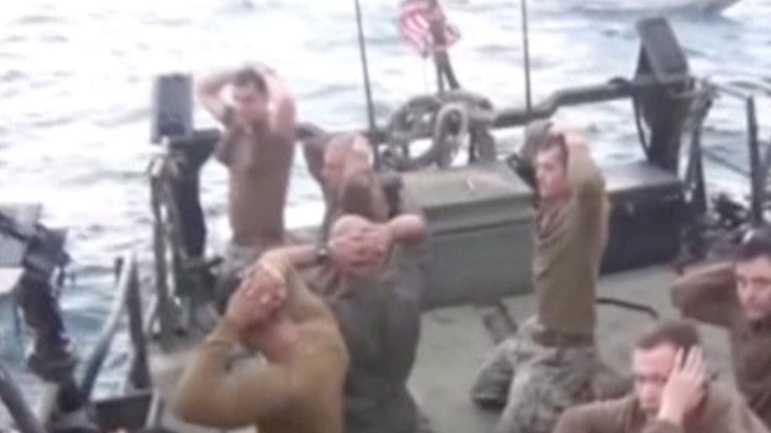 U.S. sailors are pictured on a boat with their hands on their heads at an unknown location
