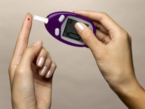 A woman using a diabetes test kit