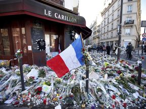 """A French flag flies over flowers, candles and messages in tribute to victims outside """"Le Carillon"""" restaurant a week after a series of deadly attacks in the French capital Paris"""
